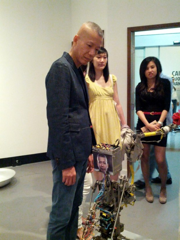 Cai Guo-Qiang with the robot Cai Guo-Qiang Fire Ignition Robot.  So meta your head will explode.  Photo by Karen Chen, courtesy Cai Studio.