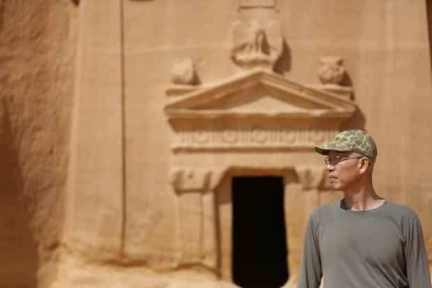 Cai Guo-Qiang standing in front of the Nabatean tombs of Mada'in Saleh, Saudi Arabia, 2013 Photo by Shu-Wen Lin, courtesy Cai Studio