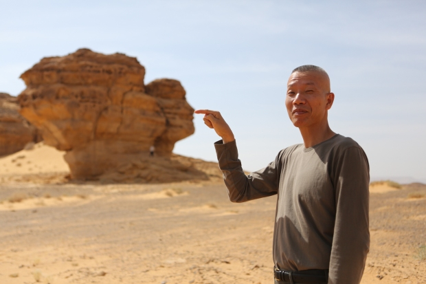 Cai Guo-Qiang posing with a rock in Mada'in Saleh, Saudi Arabia, 2013 Photo by Shu-Wen Lin, courtesy Cai Studio