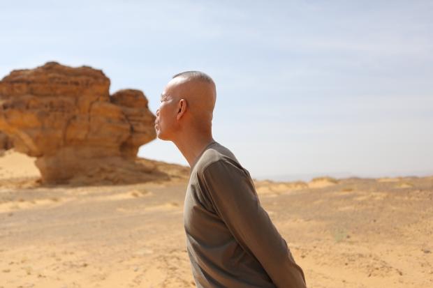 Cai Guo-Qiang posing with a rock in Mada'in Saleh, Saudi Arabia, 2013 Photo by Shu-Wen Lin, courtesy Cai Studio