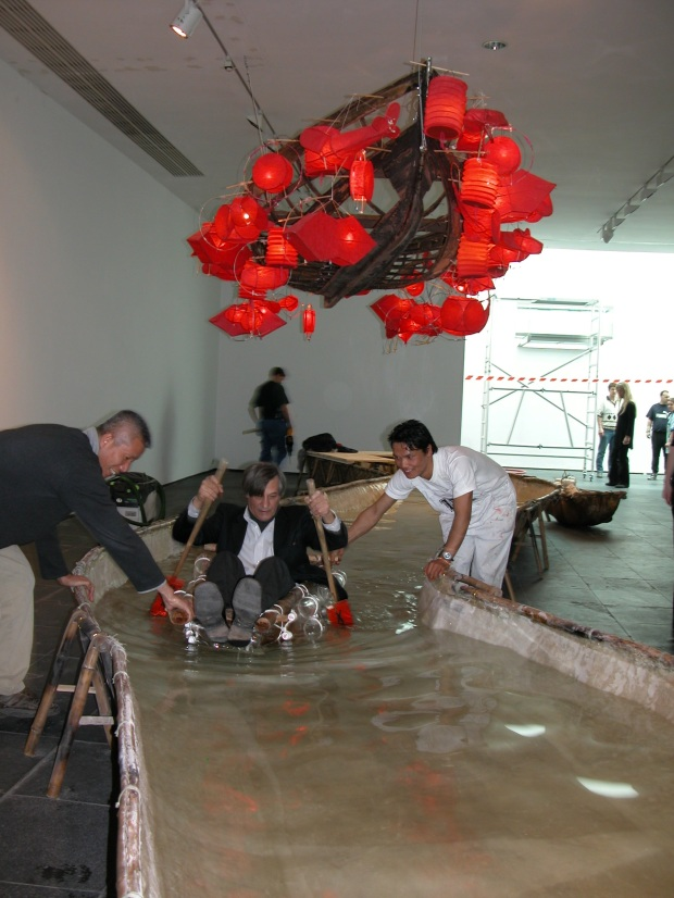 Cai Guo-Qiang assisting curator Jan Hoet riding raft on An Arbitrary History: River at S.M.A.K. Museum of Contemporary Art, Ghent, Belgium, 2003. Photo by Dirk Pauwels, courtesy S.M.A.K. Museum of Contemporary Art