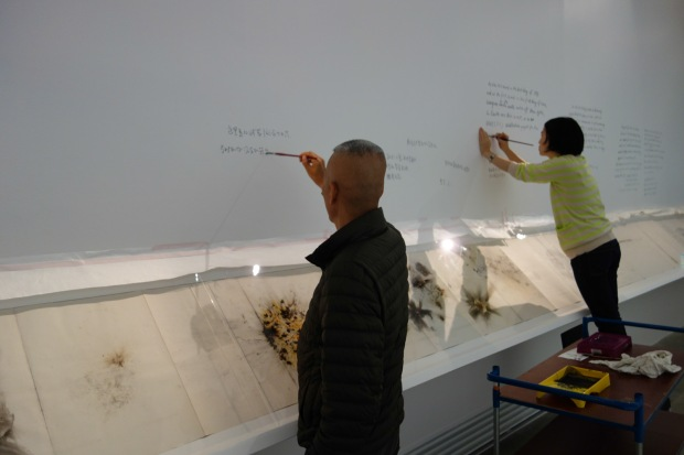Cai Guo-Qiang and project director, Chinyan Wong, writing on the wall during installation process of Cai and Hong Hong at Fondation Cartier, 1993,  Paris, France, 2014 Photo by Mariluz Hoyos, courtesy of Cai Studio