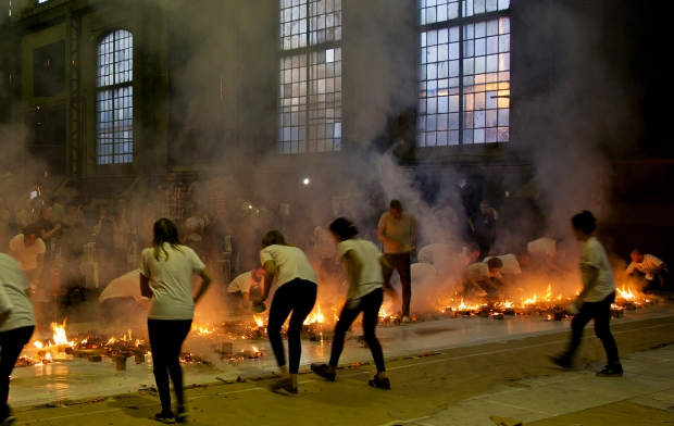Cai Guo-Qiang and volunteers rushing in to put out flames from ignition of gunpowder drawing Sentinels of the Enchanted Valley, Galpón de la Boca, Buenos Aires, 2014. Photo by Wen-You Cai, courtesy Cai Studio.